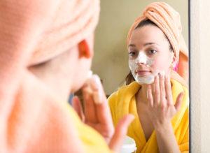 Woman after shower in bathroom mirror using a facial scrub