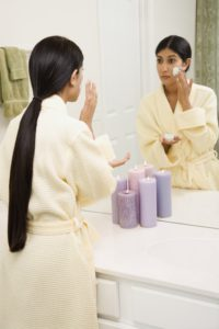 Young woman applying facial scrub.